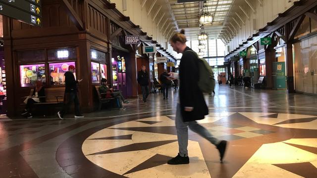 En man kollar telefonen på Göteborgs central