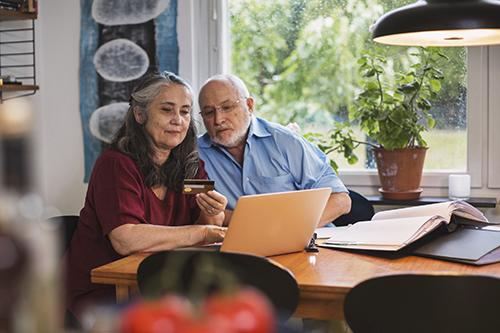 Äldre par som betalar räkningar vid köksbord