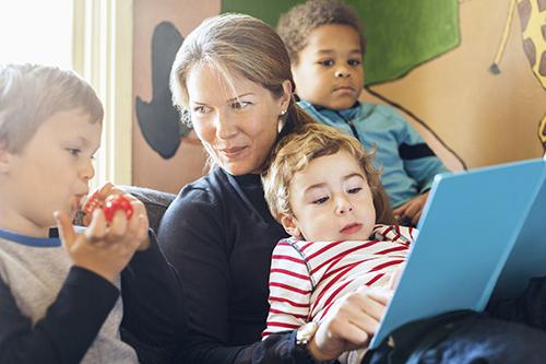 En förskolelärare läser böcker för barnen.