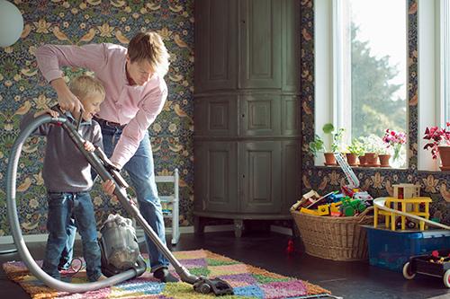En man och en pojke dammsuger en matta.