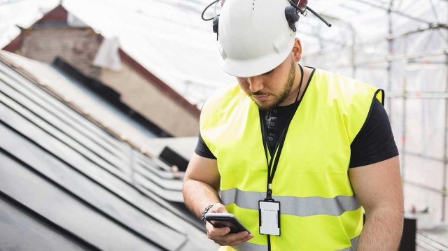 Byggnadsarbetare anv‰nder mobiltelefon pbygge