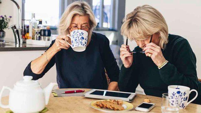 Två kvinnor dricker kaffe och tittar på en surfplatta