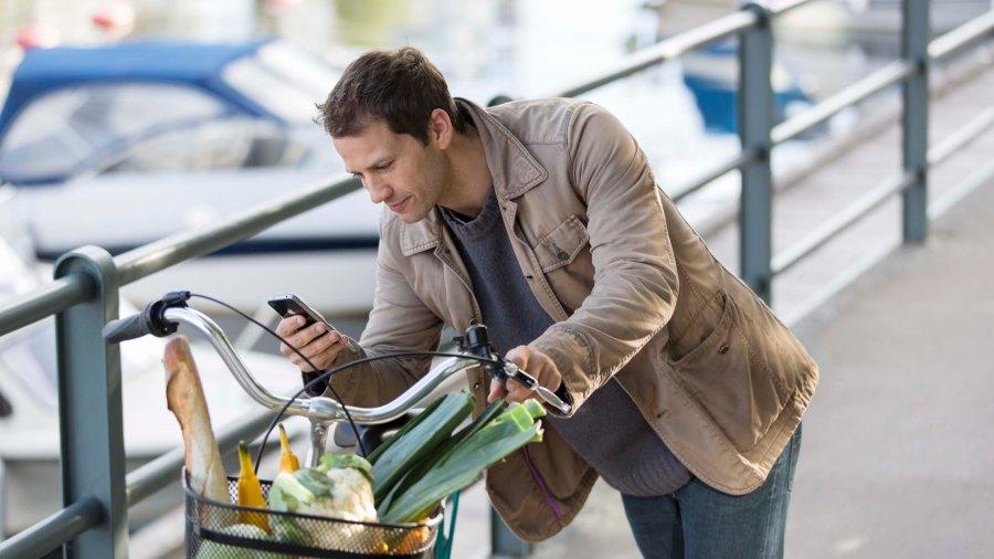 Man leder cykel och kollar sin telefon
