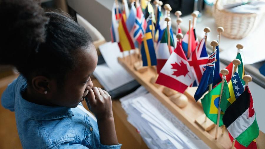 En flicka tittar på olika länders flaggor