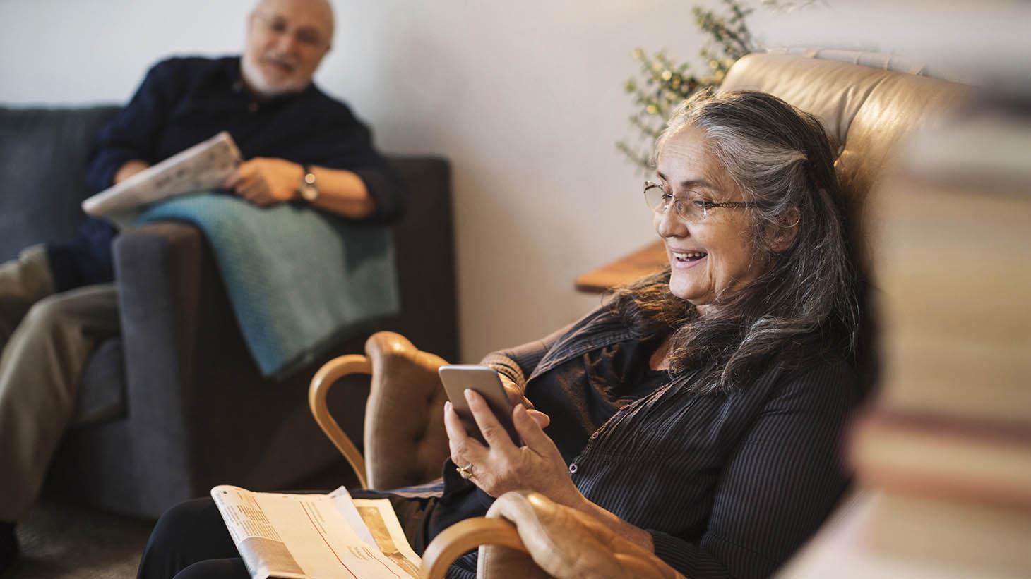 En kvinna sitter i en fåtölj och tittar på sin mobiltelefon
