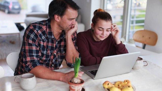 Pappa och dotter kollar på en dator, hyacint och lussebullar på bordet