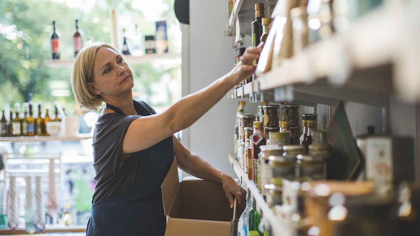 Säljare ställer fram produkter på hylla i butik