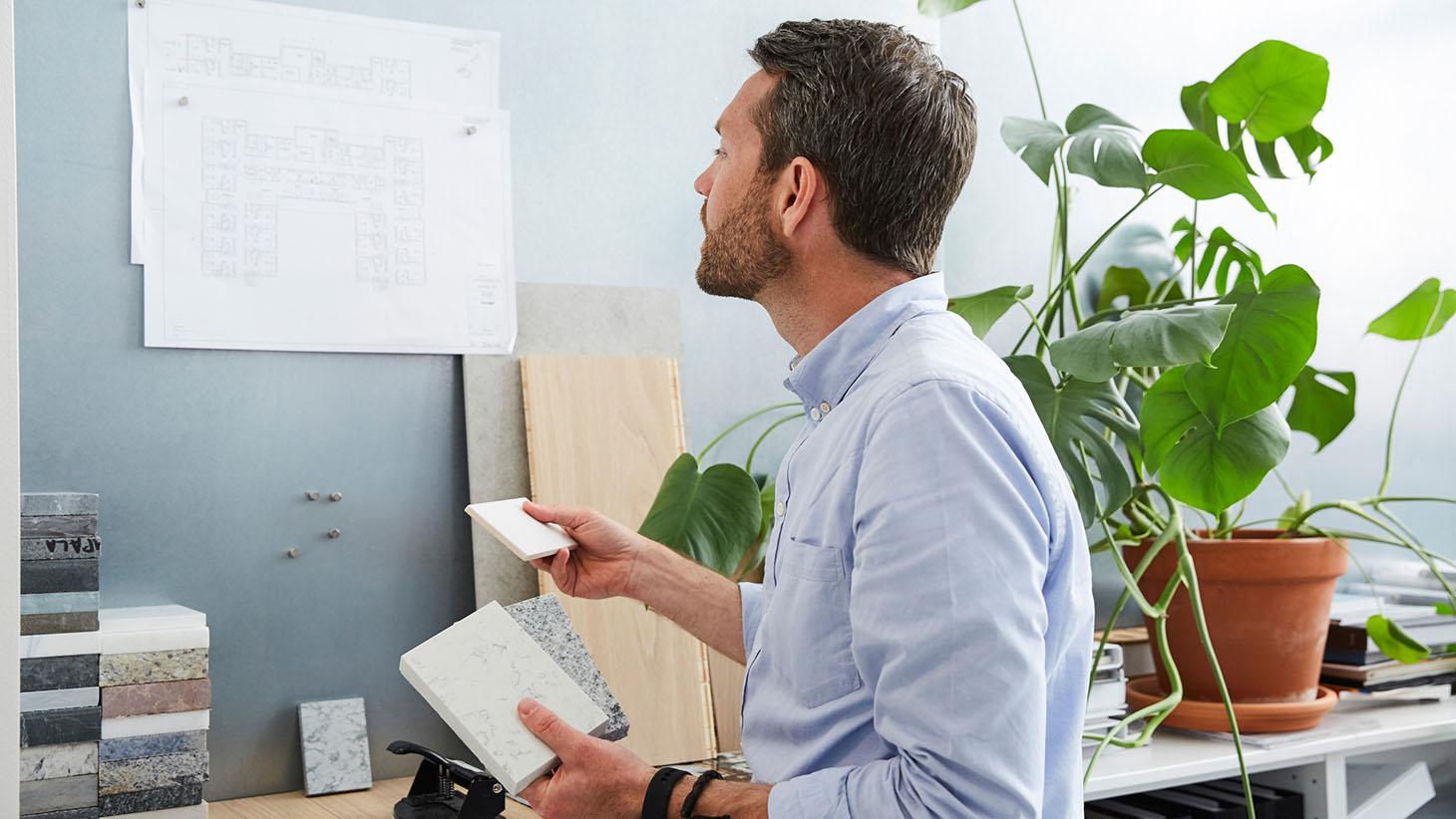 En man tittar på en ritning och väljer klinker
