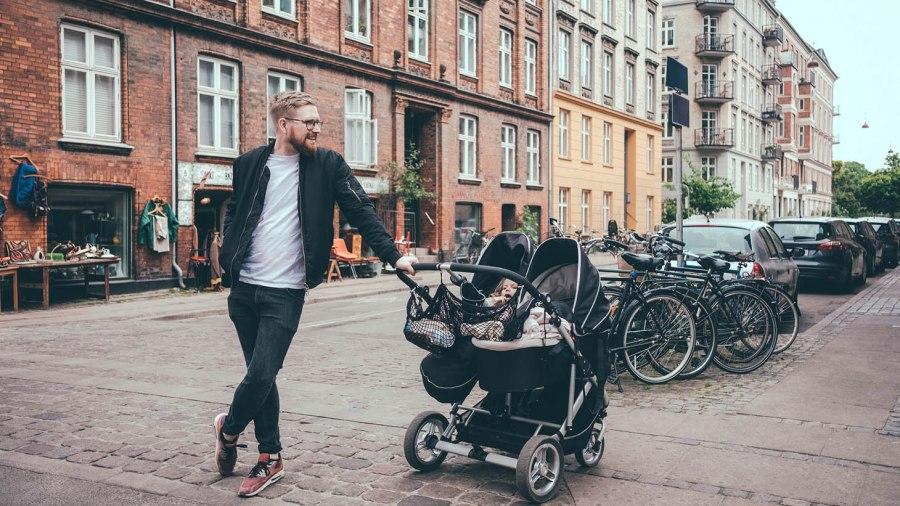 Självsäker pappa lutar sig mot barnvagn på stadsgata