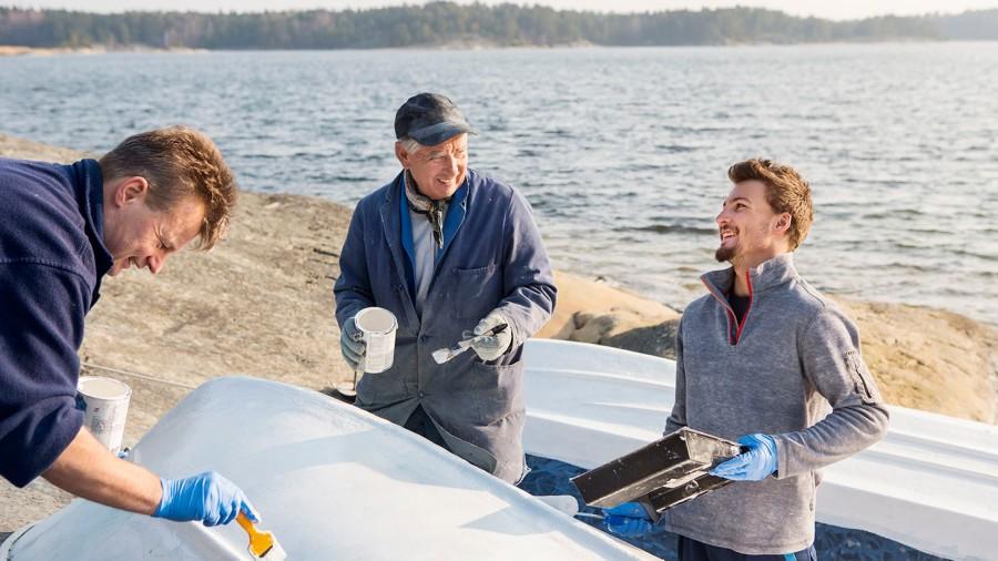Tre generationer målar båten inför sjösättning. Skärgård