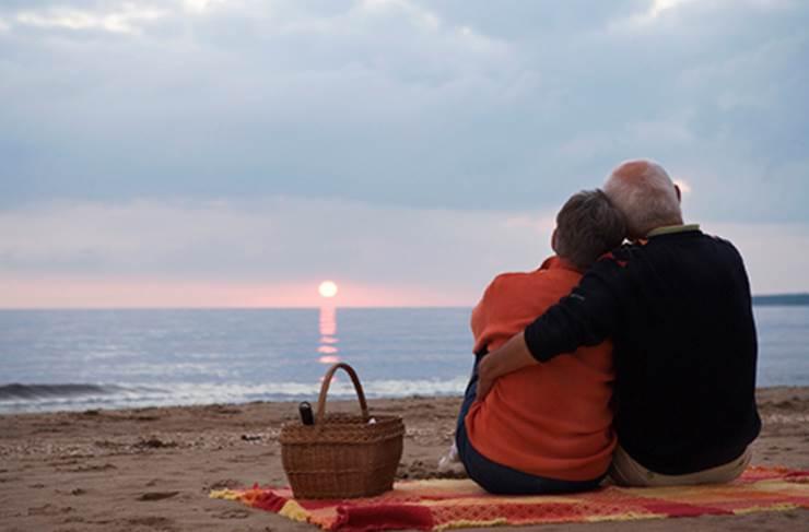 Ett par sitter på en strand i solnedgången