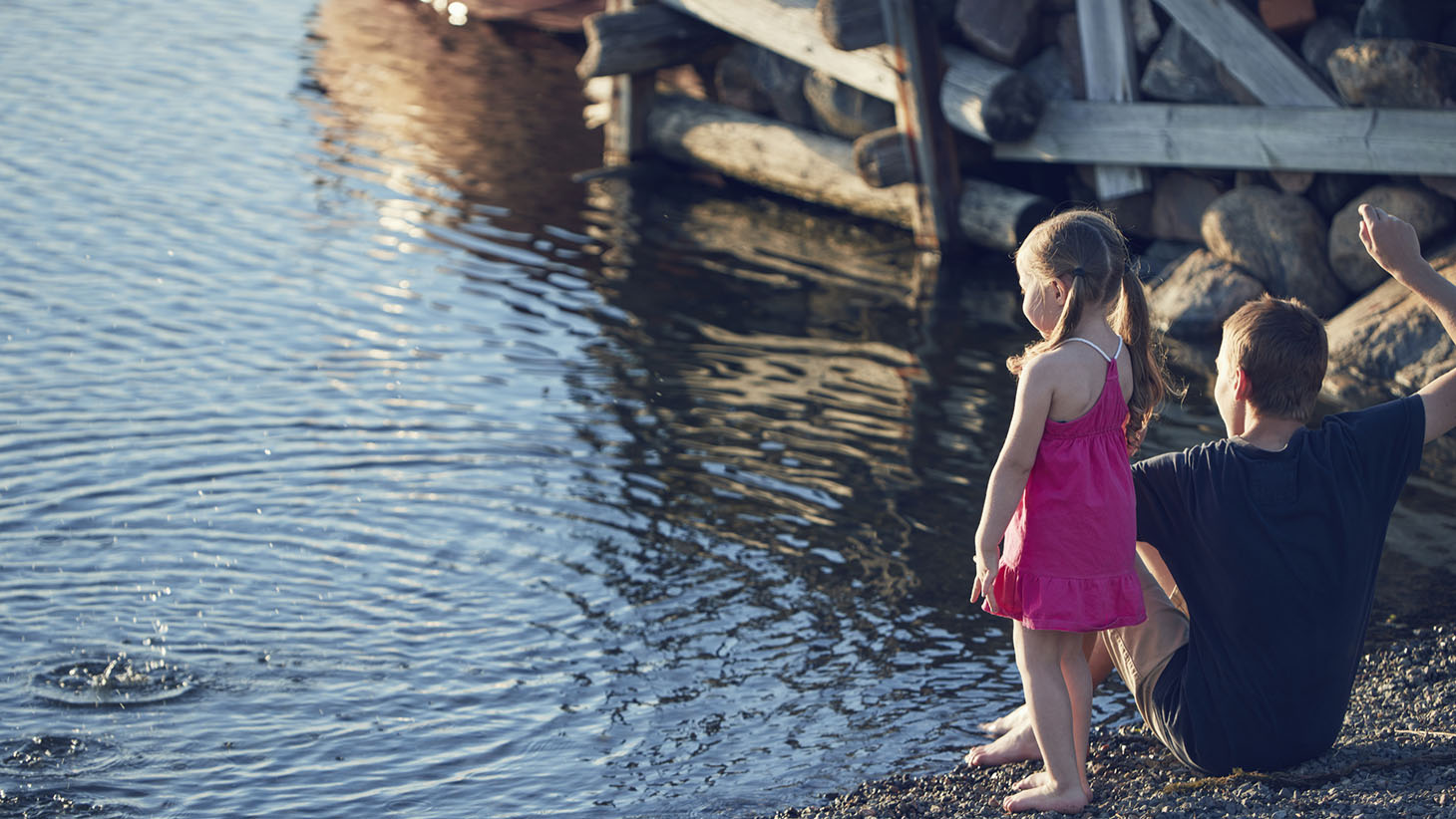 Pojke och flicka kastar sten i vatten vid foten av en brygga. Det är sommar.