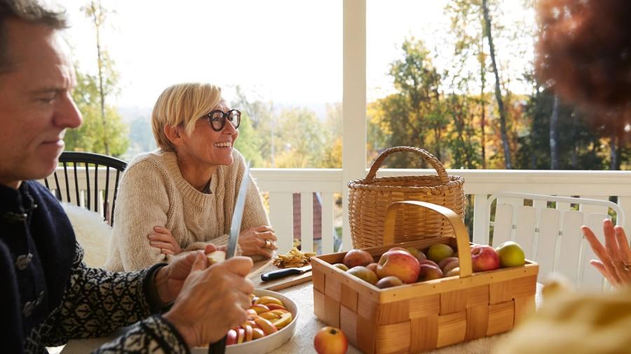En kvinna och en man sitter och skalar äpplen