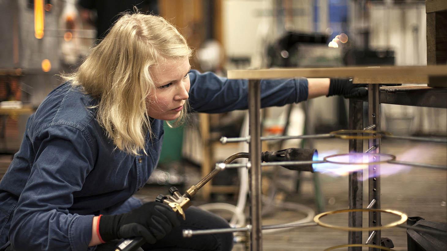 En ung kvinna svetsar på en industri