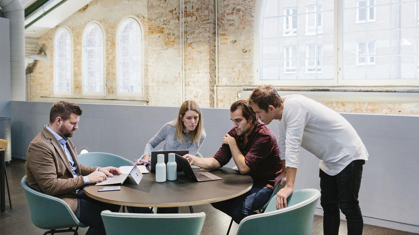 Fyra medarbetare jobbar tillsammans i en kontorsmiljö