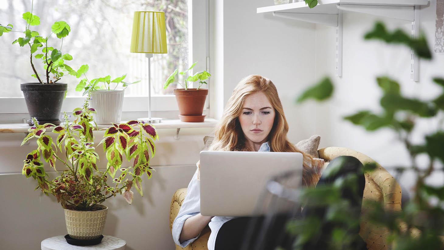 Ung kvinna sitter i en fåtölj hemma med datorn i knät