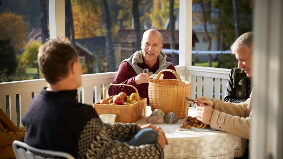 män sitter vid ett bord och rensar svampar. Äpplen i korg.
