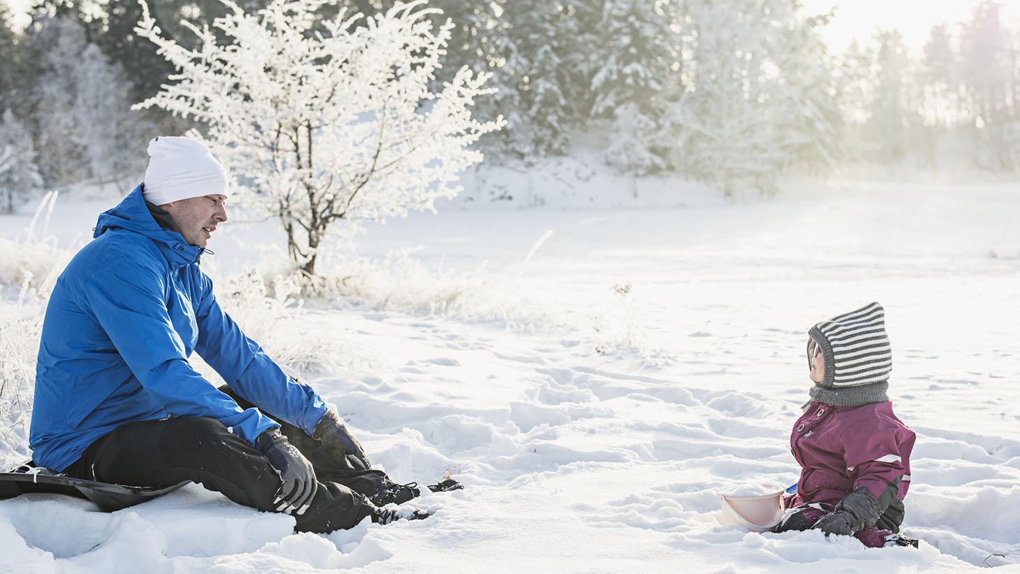 En pappa och ett barn sitter i snön och tittar på varandra