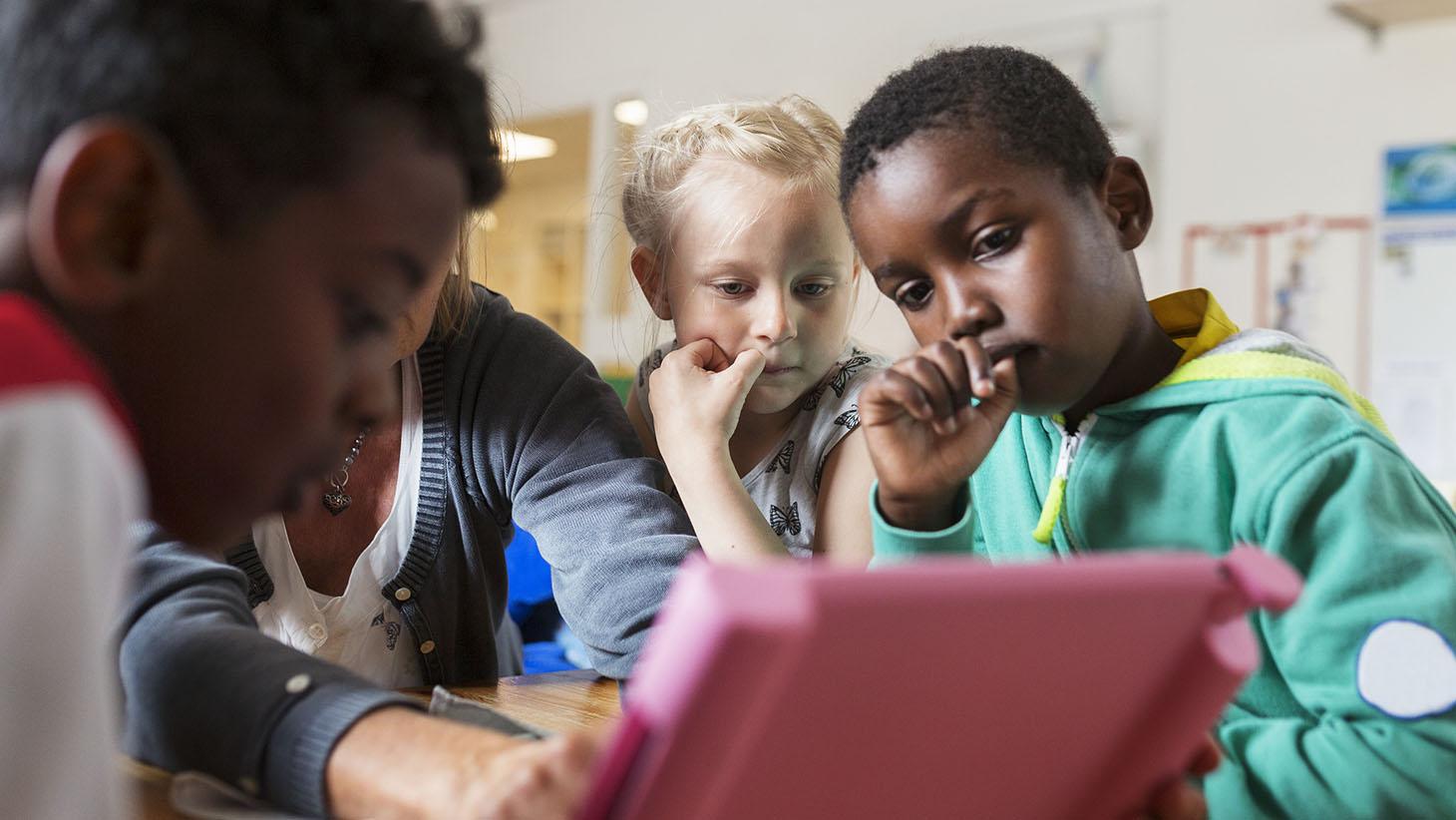 tre barn i förskoleålder sitter vid ett bord, tillsammans med en pedagog och tittar på en surfplatta