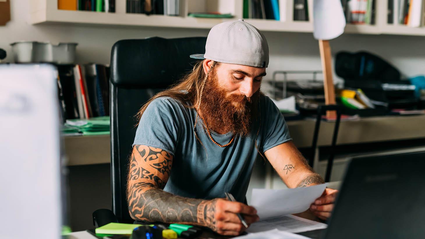 en man i 35-årsåldern sitter vid ett skrivbord och granskar ett papper