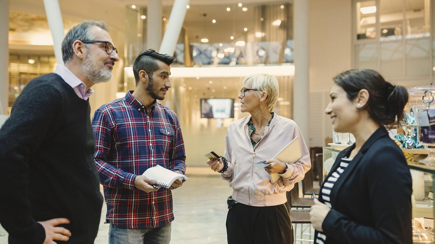 Fyra personer står och pratar på ett kontor