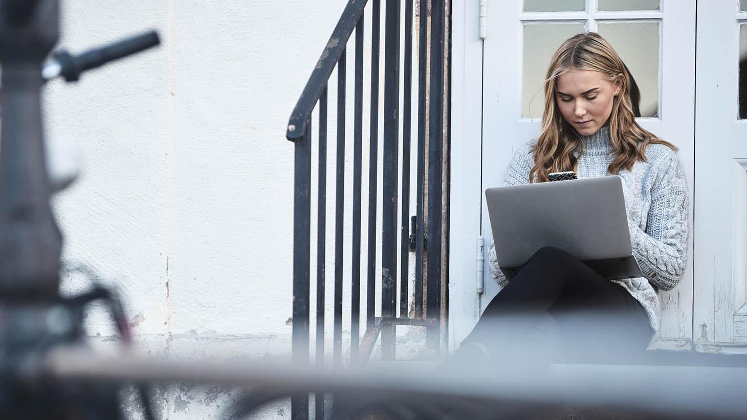 En kvinna sitter på trappan med en dator och mobil