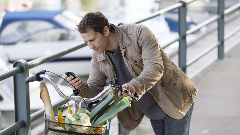 Man med cykel kollar i sin mobiltelefon