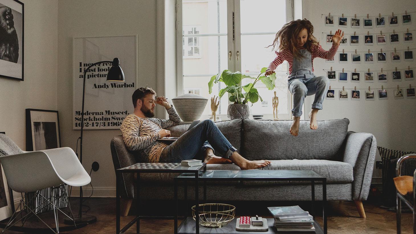 Man sitter i en soffa och tittar på datorn medan en flicka hoppar bredvid honom i soffan.