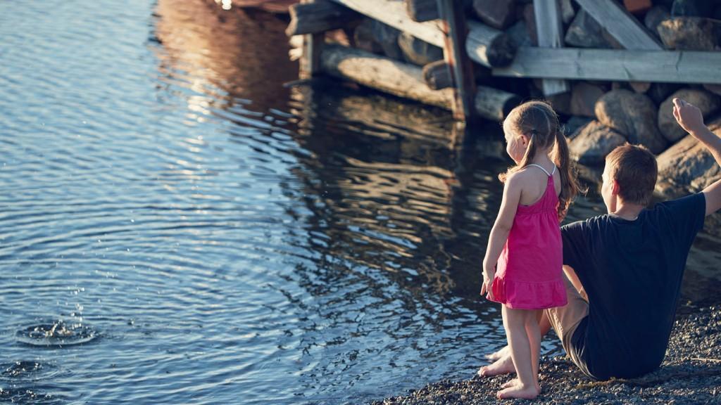två barn vid strandkanten kastar sten i havet