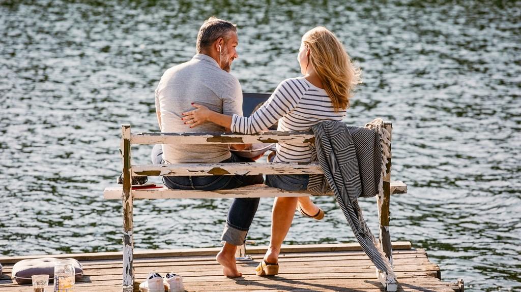 en kvinna och en man sitter på en bänk på en brygga och tittar på en dator tillsammans.