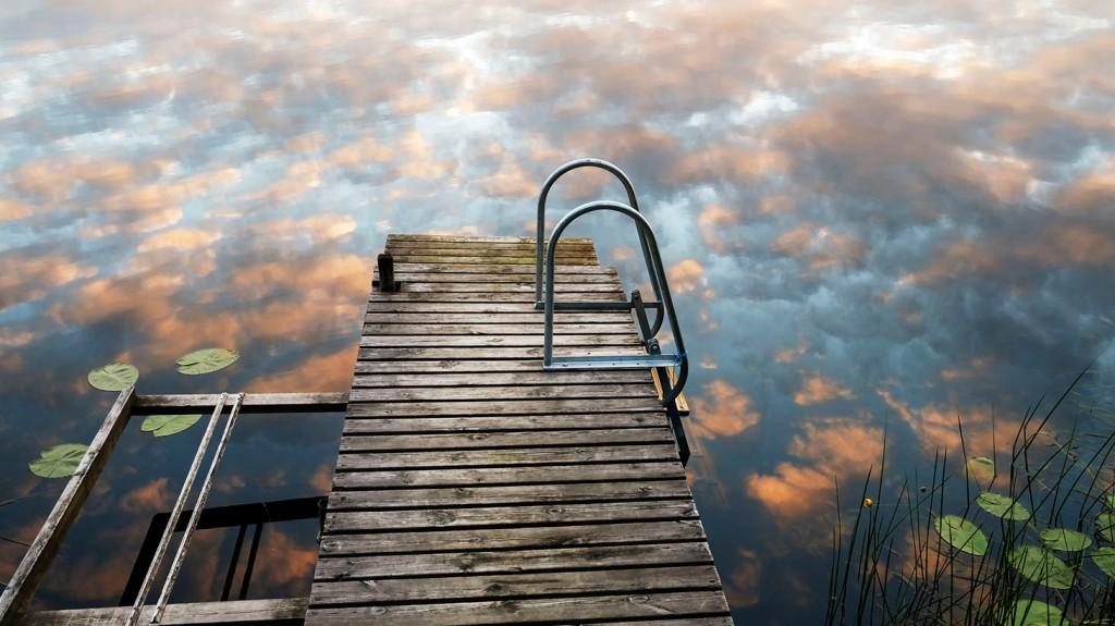 moln speglar sig i vattnet vid brygga