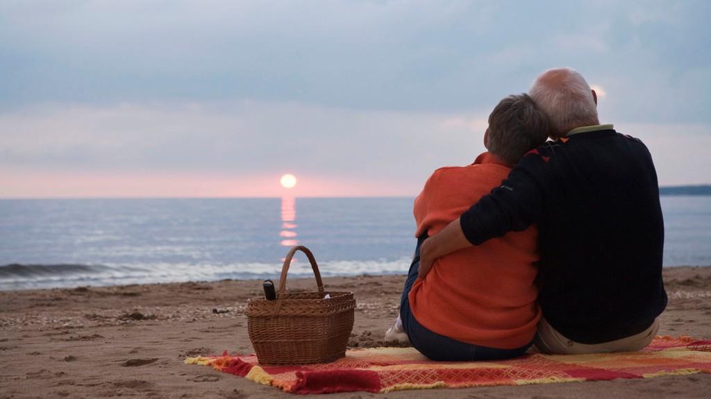 Ett äldre par sitter på en strand i solnedgången