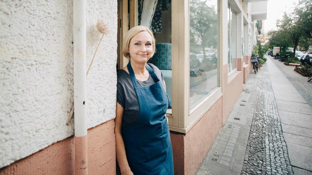 En kvinna står i dörren till sin tapetserar-verkstad.